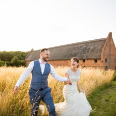 bride and groom in field in front of thatched great barn in norfolk countryside