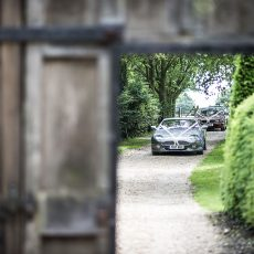 bride in wedding car approaching the grade I thatched barn the morning of her wedding before the ceremony