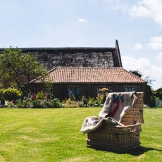 lawn games in front of hales hall thatched barn and garden room accommodation in norfolk