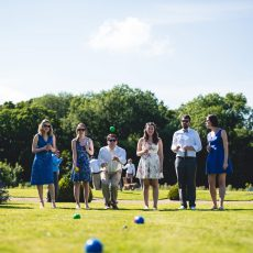 wedding guests playing on lawn at wedding reception in summer at Hales Hall Norfolk