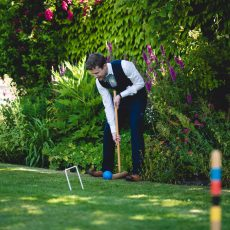 groom playing croquet at his wedding in the summer on the lawn after civil marriage ceremony norfolk