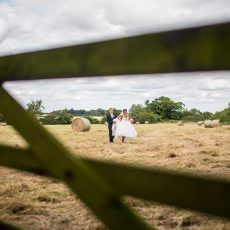 bride and groom in field at hales hall norfolk countryside