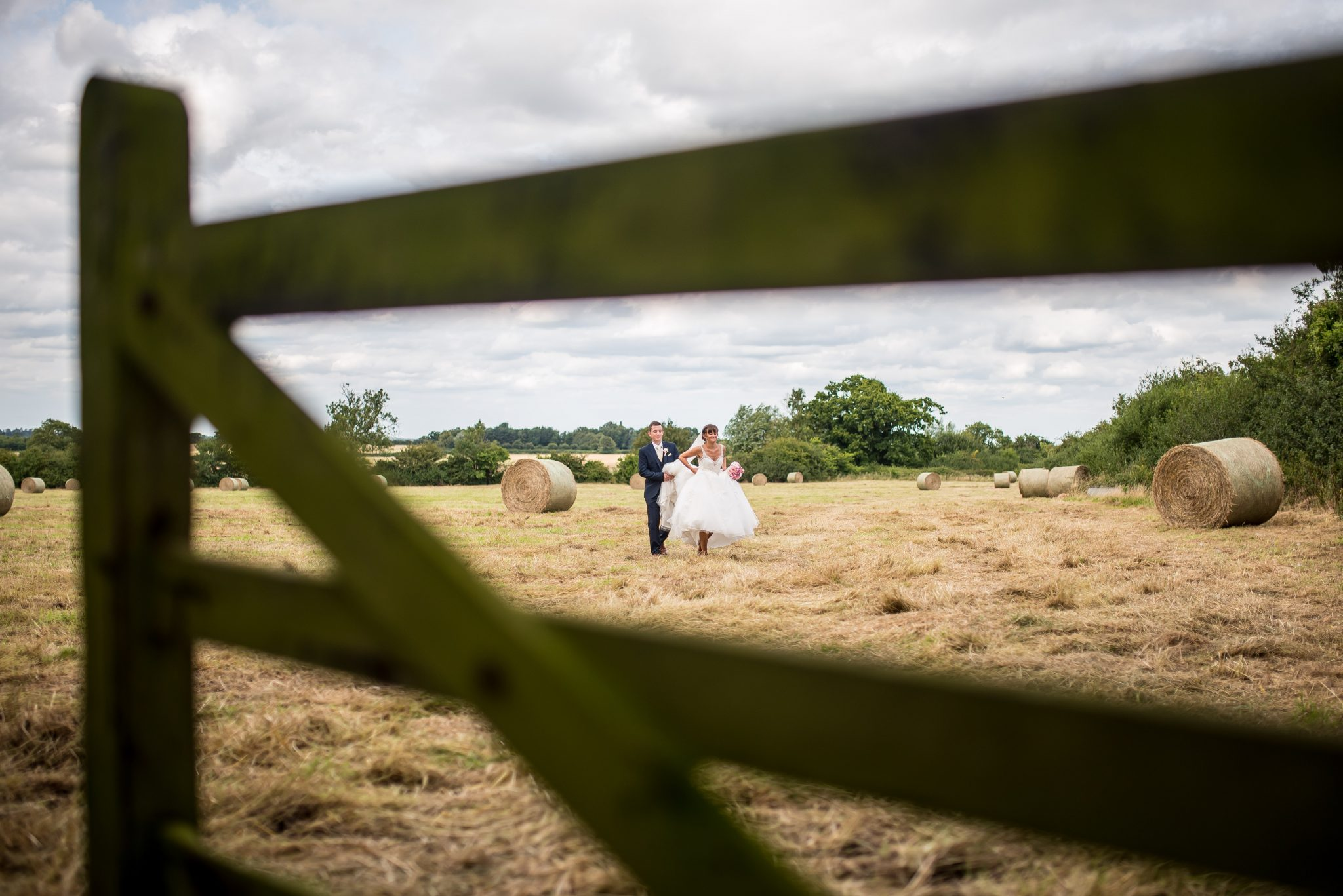 bride and groom with straw bales in field at Hales Hall Norfolk
