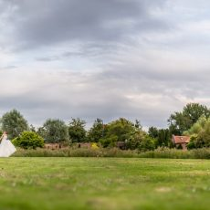 bride and groom walking in beautiful grounds at hales hall norfolk