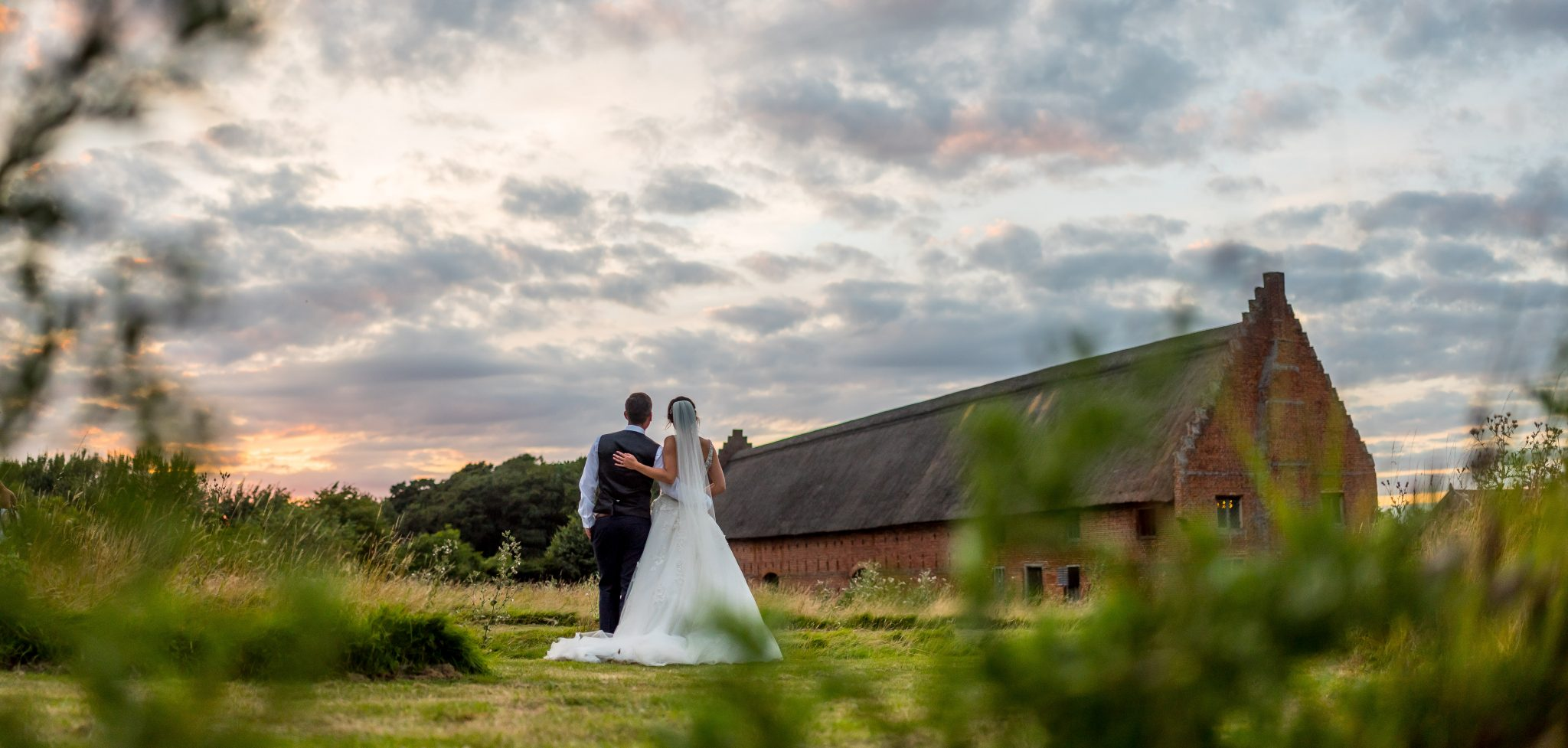 bride and groom looking at barn in Norwich taken by Daniel lightening photography