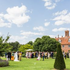wedding guests at drinks reception after wedding ceremony at Hales Hall norfolk photo by Tatum Reid photography