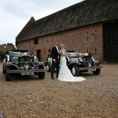 bride and groom with wedding cars outside grade I listed thatched barn