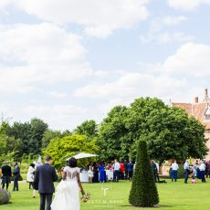 bride and groom on lawn at hales hall and the great barn in Norfolk