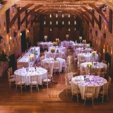inside tudor grade I listed thatched barn table set up for wedding in Norwich norfolk