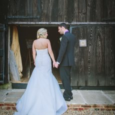 bride and groom outside their wedding venue after getting married at hales hall and the great barn in norfolk Suffolk border