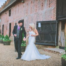 bride and groom leaving the Great Barn after getting married at their wedding ceremony hales hall