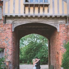 bride and groom under archway of hales hall wedding venue in norfolk