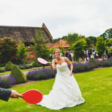 Bride and Groom playing lawn games at Hales Hall in front of thatched barn norfolk