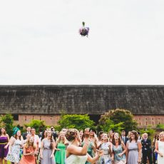 bride throwing her bouquet in front of largest thatched brick barn in Britain at her wedding