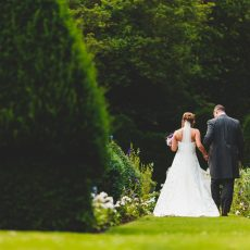 bride and groom in long landscaped garden at hales hall norfolk Suffolk