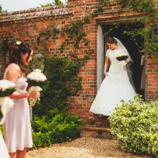 bride coming out of cottage on the morning of her wedding with bridesmaids holding a bouquet at hales hall