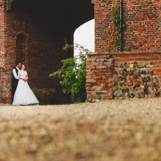 bride and groom under archway at hales hall country estate norfolk