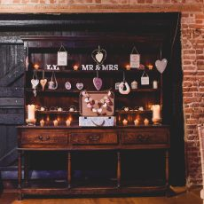 Antique dresser decorated at wedding reception in thatched tudor barn at Hales Hall Norfolk