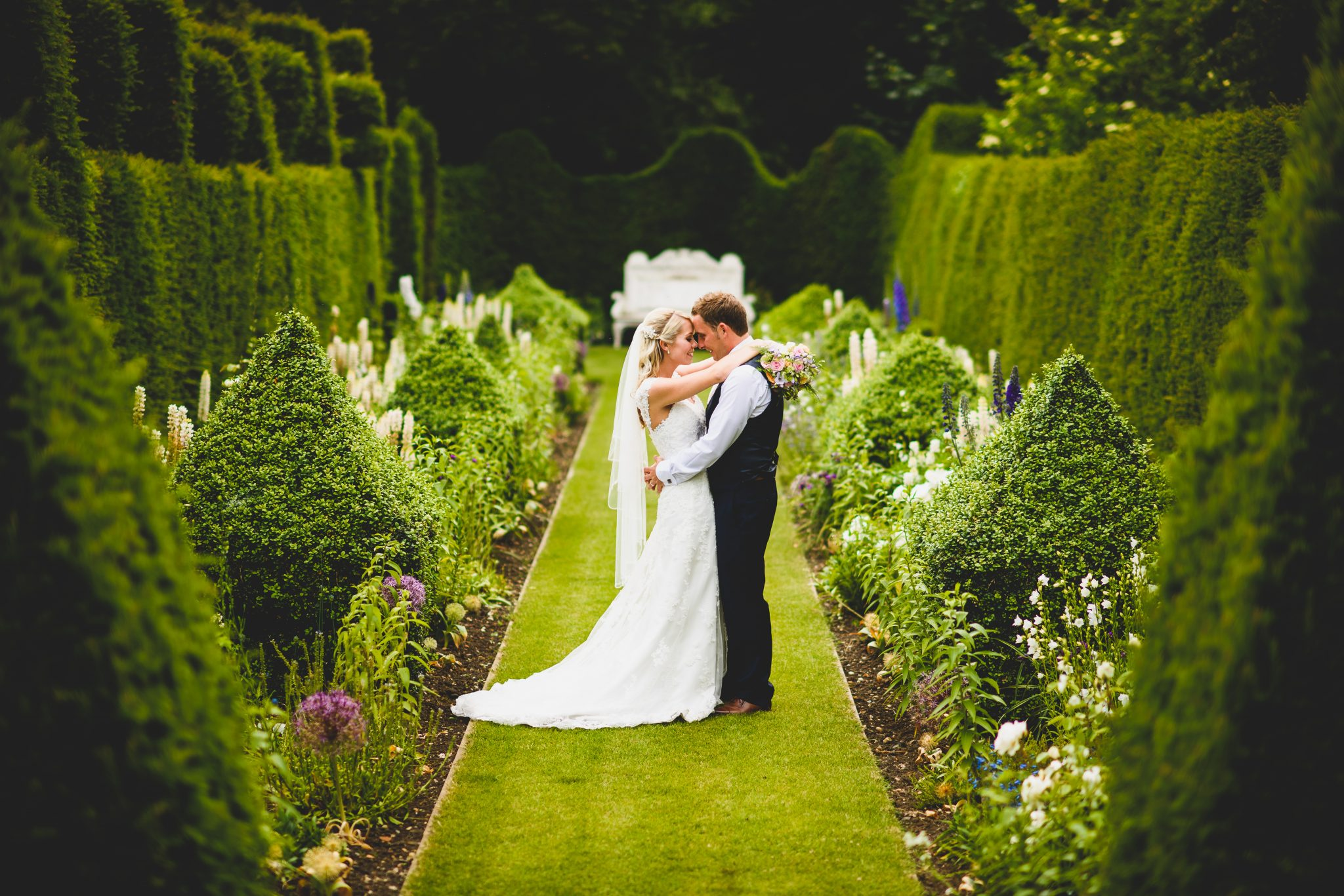 bride and groom in long topiaried gardens photographed by James Rouse Photography