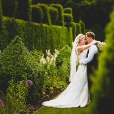 bride and groom in landscaped gardens at hales hall Norwich