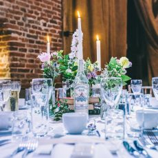 table decorations at hales hall barn norfolk at liann and tom's wedding candles gin and books for decorations