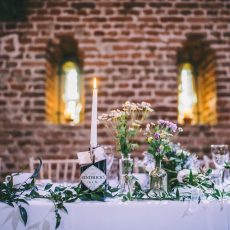 candles in gin bottles and candles in 170 loop hole windows at wedding reception in Loddon norfolk