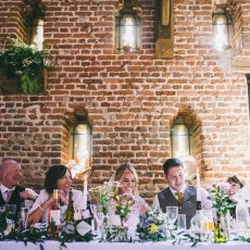 top table at wedding reception with loophole windows in the background of brick thatched tudor barn