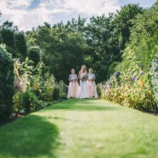 bride with her bridesmaids enjoying the gardens at Hales Hall & The Great Barn, photography by James Powell Photography