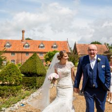 Bride's father walking his daughter, the Bride to the oldest surviving brick tudor barn in Britain. Hales Hall and The Great Barn Loddon