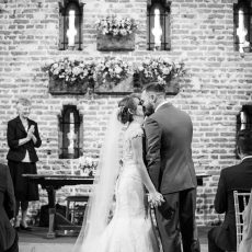 bride and groom tying the knot infront of the loop holed windows in the Brick Tudor Barn Norfolk Loddon