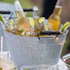 bottles of Corona in a bucket for wedding reception drinks on lawn at Hales Hall & The Great Barn norfolk