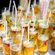 glasses of pimms served after wedding ceremony on front lawn at Hales Hall & the Great Barn Loddon Norfolk