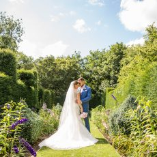 bride and groom in landscaped gardens at hales hall great thatched barn in norfolk