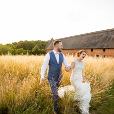 bride and groom in fields at Hales Hall in front of the Great Barn in Loddon Norfolk