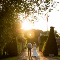 bride and groom in gateway at hales hall at sunset in norfolk